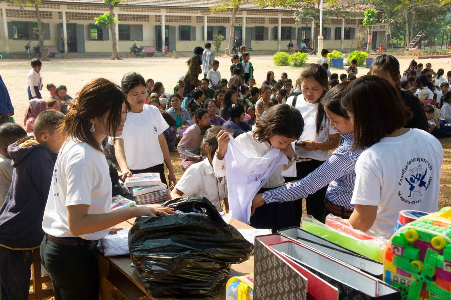 Toute l'équipe de volontaires à l'action pour la distribution des sacs de riz dans une école au Cambodge