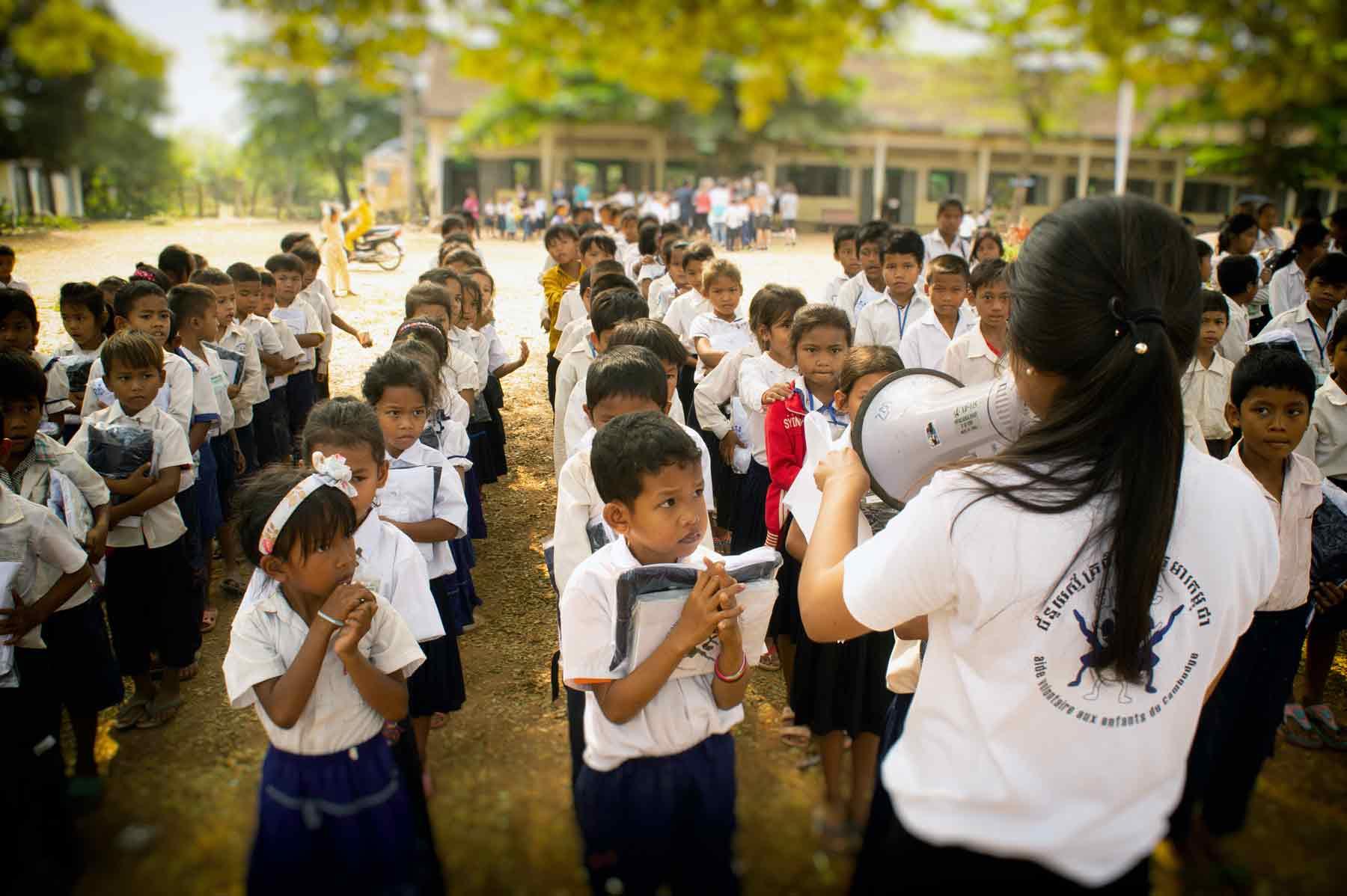 Jeune volontaire au Cambodge lors d'une action humanitaire liée à l'éducation avec des centaines d'enfants dans une école publique.